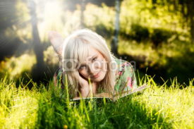 Obrazy i plakaty Young girl lies on green grass and reads book