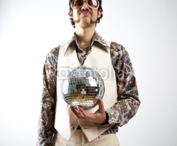 Naklejki Portrait of a retro man in a 1970s leisure suit and sunglasses holding a disco ball - mirror ball