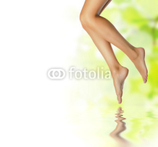 Naklejki healthy sexy slender female legs over spring background