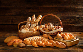 Naklejki Variety of bread in wicker basket on old wooden background.