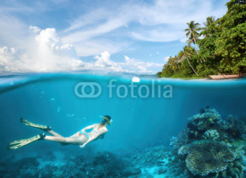 Naklejki Young woman snorkeling in clear tropical waters in near of exotic island.
