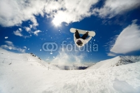Fototapety Snowboarder going off jump doing a backflip