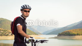 Fototapety Mountain biker beside a beautiful lake