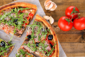 Fototapety Pizza with arugula on color wooden background