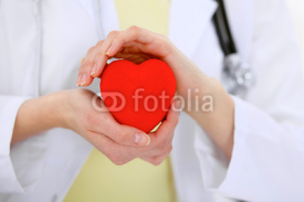 Obrazy i plakaty Female doctor with stethoscope holding heart.  Patients couple sitting in the background
