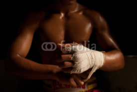 Fototapety The muscular fighter tying tape around his hand preparing to box