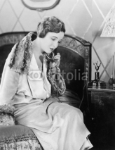 Fototapety Young woman sitting on her bed in the bed room, speaking on the telephone