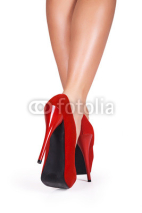 Naklejki Woman legs wearing red high heels isolated on white background.