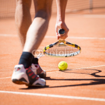 Obrazy i plakaty sportsman catchs up his tennis ball with racket