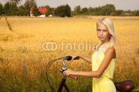 Obrazy i plakaty Young girl with a bike in the countryside.