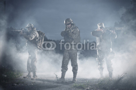 Obrazy i plakaty NATO soldiers in full gear. In a defensive posture. Preparing to attack.