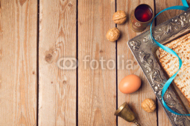 Jewish holiday Passover concept with matzah, seder plate and wine on wooden background. View from above