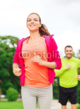 Obrazy i plakaty smiling couple running outdoors