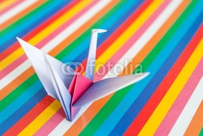An origami bird on a colorful stripes background.