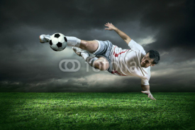 Naklejki Football player with ball in action under rain outdoors