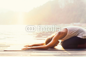 Fototapety Sun salutation yoga. Young woman doing yoga by the lake, bathing in sunlight.