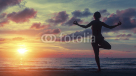 Fototapety Yoga woman exercising on the beach during a stunning sunset. Peace, harmony, health and meditation.