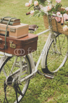 Obrazy i plakaty Vintage bicycle on the field with a basket of flowers