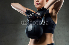 Obrazy i plakaty close up of woman with kettlebell in gym