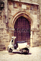 Naklejki White vintage scooter near medieval gate