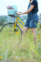Obrazy i plakaty Young woman with bicycle in meadow