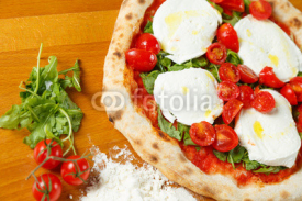 Obrazy i plakaty Typical Italian Pizza, ingredients in background on wood table