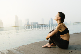 Fototapety Relaxed young yoga woman in yoga pose near pool.