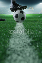 Fototapety Close up of foot on top of soccer ball on the line, side view, stadium