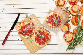 Fototapety Small pizzas on baking paper close up