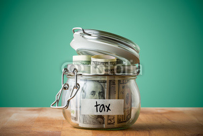 Dollar bills in glass jar isolated on a green background. Saving money concept for tax.