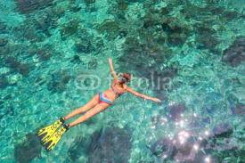 Woman snorkeling in clear tropical waters above coral reef