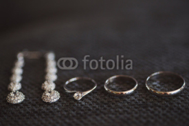 Obrazy i plakaty wedding rings and engagement ring and long earrings on dark textured background