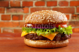 Naklejki Hamburger on table with red brick wall background