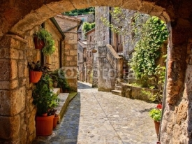 Naklejki Arched cobblestone street in a Tuscan village, Italy
