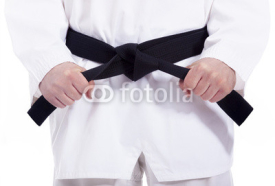 Fototapety Martial arts man tying his black belt, isolated on white