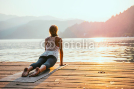Fototapety Yoga sun salute. Young woman doing yoga by the lake at sunset