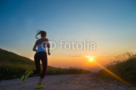 Obrazy i plakaty woman running on a mountain road at summer sunset