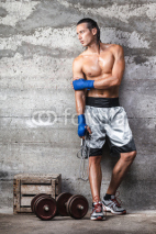 Fototapety attractive boxer man standing on the wall and looking aside