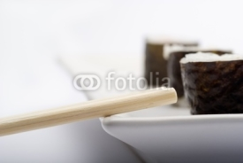 Fototapety Composition of maki sushi, white late and a stick.