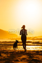 Obrazy i plakaty Woman and dog running on beach at sunrise