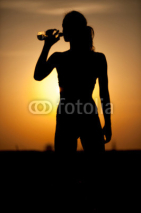 Fototapety silhouette of a young sportive woman drinking water