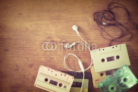Naklejki Top view (above) shot of retro tape cassette with earphone on wood table - vintage color effect styles.