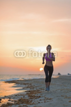 Naklejki Fitness young woman running on beach in the evening