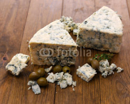 Obrazy i plakaty Tasty blue cheese with olives, on wooden table