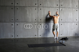 Obrazy i plakaty Man at the wall in the gym resting after exercise