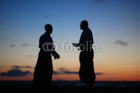 Fototapety Silhouettes of two men speaking at sunset