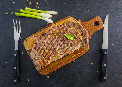 Grilled beef steak served on a wooden board.
