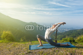 Fototapety Woman does yoga asana Anjaneyasana in mountains