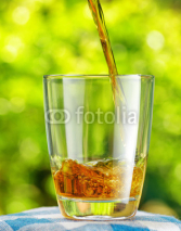 Naklejki Glass of apple juice on nature background