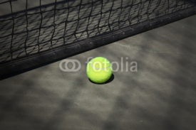 Fototapety Tennis ball on the court with the net on the background